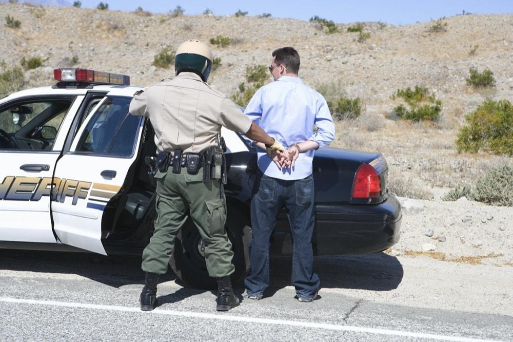 Policeman arresting criminal on road